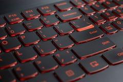 Closeup of gamer laptop keyboard red illumination, backlit keyboard, english letters royalty free stock images