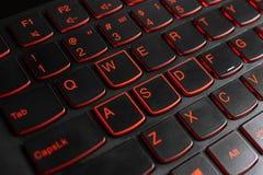 Closeup of gamer laptop keyboard red illumination, backlit keyboard, english letters stock images