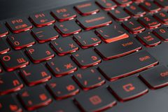 Closeup of gamer laptop keyboard red illumination, backlit keyboard, russian letters.  royalty free stock photography