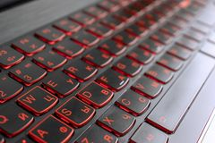 Closeup of gamer laptop keyboard red illumination, backlit keyboard, russian letters royalty free stock photography