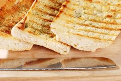 Closeup garlic bread with knife Stock Photography