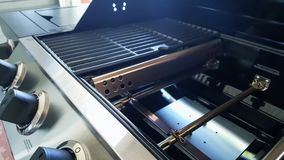 Closeup of Gas Barbecue Grill burners, flavorizer bars, porcelanized cast iron grids, and control knobs. Stock Photo