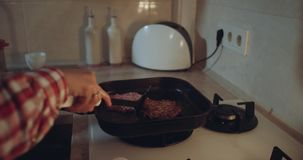 Closeup at the gas hob woman turns the burgers from the pan.  stock footage