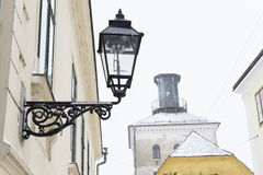 Gas lantern and Lotrscak Tower. Closeup of a gas lantern in Zagreb, Croatia, with a view of Lotrscak Tower in the background, during a snowstorm Stock Image