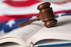 fbc65206ffc5 Closeup of a Gavel on Open Book and American Flag. Law gavel legal system  book