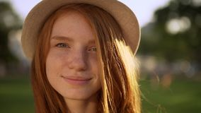 Closeup gentle attractive lady in hat with nice red long hair looking at camera touching hair smiling during bright stock video footage