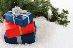 Closeup of gift boxes and pine branch on abstract snow. Stock Image