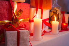 Closeup of gifts near a Christmas tree in the candlelight Royalty Free Stock Images