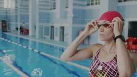 Closeup gimbal shoot. Confident female swimmer getting ready to swimming pool putting on her goggles for underwater. Floating, She wear swimsuit and red swim stock video footage