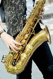 Closeup of a girl with a beautiful golden saxophone. Closeup of a girl with a beautiful golden saxophone in the park Royalty Free Stock Photography