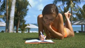 Girl Smooths Hair Tans on Grass Beach at Palms Closeup. Closeup girl in bikini tans on grass beach smooths long hair waving by wind writes in paper book against stock footage