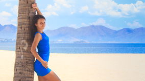 Closeup girl in blue leans on palm trunk under palm shadow. Camera approaches long-legged girl in blue frock barefoot leaning on palm trunk under palm shadow stock footage