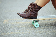 Closeup girl with boots sitting on skate board Royalty Free Stock Images