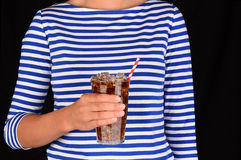 Closeup Girl With Cold Glass of Soda. Closeup of a girl holding a cold glass of soda in front of her torso. A red a white striped straw is in the glass and the Stock Photo