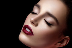 Closeup of girl with dark red lips. Closeup of young woman with dark red lips. Closed eyes. Over black background. Copy space Stock Photo