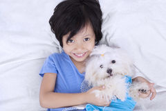 Closeup of girl and dog on bed. Unique perspective of lovely little girl smiling at the camera while holding a maltese dog in the bedroom Stock Images