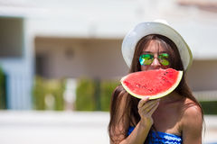 Closeup girl in hat and sunglasses with watermelon Royalty Free Stock Image