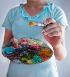 Closeup of girl holding brushes and palette Royalty Free Stock Photo