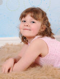 Closeup of girl laying on a furry brown rug Royalty Free Stock Photo