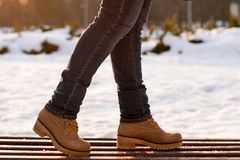Closeup girl legs in jeans in beige boots standing on wooden bench in winter frosty sunny day on blurred background. Casual style stock image