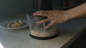 Girl Adds Fresh Milk to Ground Flakes in Blender. Closeup girl with nice red manicure adds fresh milk to ground flakes in blender and peeled bananas in stock video