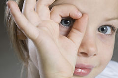 Closeup Of Girl Peeking Through Hand Stock Photo