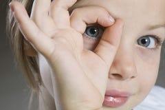 Closeup Of Girl Peeking Through Hand. Closeup portrait of a young girl peeking through hand against gray background stock photo