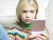 Closeup Of Girl Playing Handheld Video Game Stock Photography