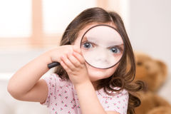 Closeup of girl playing with magnifying glass. Stock Photo