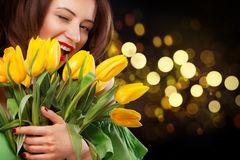 Closeup girl portrait. Beautiful brunette woman smiling with tulip flowers in hands on black background with bokeh Stock Photography