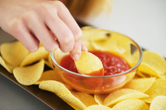Closeup on girl putting chips in sauce Royalty Free Stock Photos