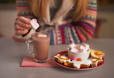 Closeup on girl putting marshmallow into cup of chocolate royalty free stock image