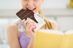 Closeup on girl reading book and eating chocolate Royalty Free Stock Photos