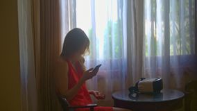 Girl Sits at Table Setups Software for Using Helmet Closeup. Closeup girl in red clothes sits at table and setups software on phone for using virtual reality stock footage