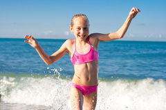 Closeup girl running from sea wave Stock Images