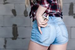 Closeup girl`s back, wrench in pocket of blue denim jeans overalls, checkered shirt. Ð¡oncept of repair in house, female labor, stock photos