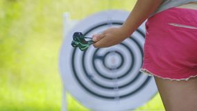 Girl in hand holds darts for darts on the nature. Closeup girl`s hand with darts for darts. Girl in hand holds darts for darts on the nature stock footage