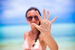 Closeup of girl's hand with heart on the palm. Close-up of girl's hand with heart on the palm painted by suncream Stock Photos