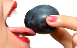 Closeup of girl's mouth and plum Royalty Free Stock Images