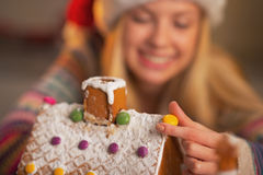 Closeup on girl in santa hat decorating christmas cookie house Royalty Free Stock Photography