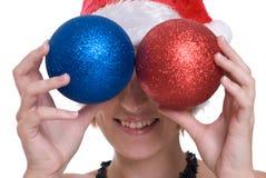 Closeup girl in santa hat and decoration balls Stock Photos