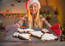 Closeup on girl in santa hat showing pan of fresh cookies Royalty Free Stock Photo