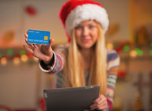 Closeup on girl in santa hat with tablet pc showing credit card Royalty Free Stock Photos