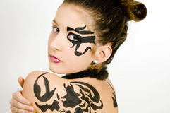 Closeup girl with scorpio painted on back. Closeup of girl with black scorpio sign painted on back and face royalty free stock photography