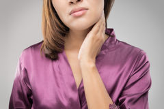 Closeup girl with sore throat touching her neck. On gray wall background royalty free stock photography