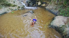 Closeup Girl Tries to Swim in Shallow Water by Waterfall stock footage