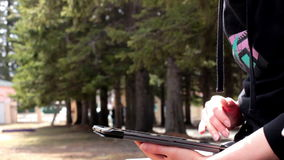 Closeup of a girl using tablet in the park. Full hd stock video