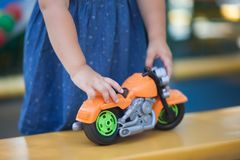 Closeup, girls hands riding toy motorcycle. Royalty Free Stock Image