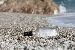 Closeup of a glass bottle stranded on the beach on sunny summer. Closeup of a glass bottle stranded on the sea beach on sunny summer day; Pollution of the stock image