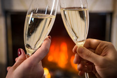 Closeup of glass of champagne in couple`s hands near fireplace Royalty Free Stock Photo